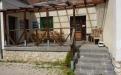 Az ugodi Árnyaserdő Turistaszálló épületbejárata padokkal és asztalokkal